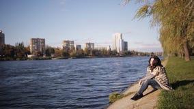 Красивая девушка наслаждается взглядом реки холодный ветер осени развивает ваши волосы мягкий солнечный свет отраженный от воды акции видеоматериалы