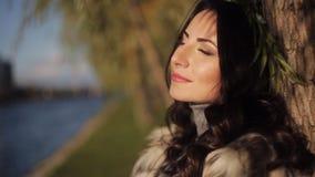 Красивая девушка на банке реки ветер осени развивает ваши волосы мягкий солнечный свет сток-видео