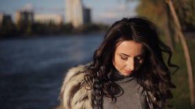 Красивая девушка на банке реки ветер осени развивает ваши волосы мягкий солнечный свет видеоматериал