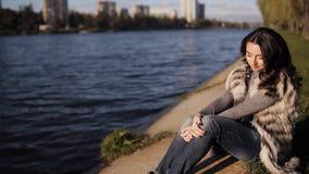 Красивая девушка на банке реки Конец-вверх мягкий солнечный свет отражен от реки видеоматериал
