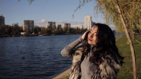 Красивая девушка на банке реки холодный ветер осени развивает ваши волосы мягкий солнечный свет видеоматериал
