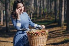 Красивая девушка на велосипеде говоря на телефоне, при темные волосы и шляпа стоя близко велосипед с корзиной Девушка лета Стоковая Фотография RF