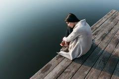 Красивая девушка на деревянной пристани около воды Стоковые Изображения RF