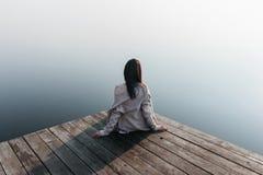 Красивая девушка на деревянной пристани около воды Стоковое Изображение RF