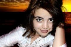 Красивая девушка на предпосылке захода солнца моря Стоковые Фотографии RF