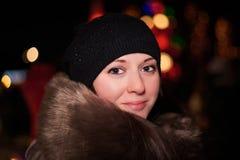 Красивая девушка на предпосылке ночи освещает Стоковая Фотография
