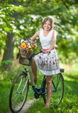 Красивая девушка нося славное белое платье имея потеху в парке с велосипедом Здоровая внешняя концепция образа жизни Винтажный пе Стоковая Фотография RF