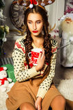 Красивая девушка около рождественской елки сидя с чашкой в ее h Стоковая Фотография