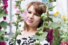 Красивая девушка окруженная красочным просвирником цветков Стоковые Изображения