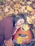 Красивая девушка отдыхая на листьях осени Стоковое Изображение