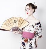 Красивая девушка одетая как гейша, она держит китайский вентилятор Состав и волосы гейши одели в кимоно Концепция  Стоковое Изображение RF
