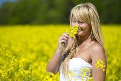 Красивая девушка пахнуть желтыми цветками Стоковые Фотографии RF
