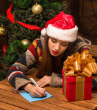 Красивая девушка писать поздравление Нового Года и рождества Стоковое Фото