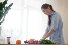 Красивая девушка подготавливая обед Стоковые Изображения RF