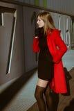 Красивая девушка представляя с красным пальто стоковое изображение rf