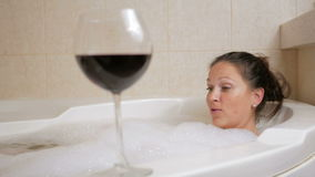 Красивая девушка принимая жемчужную ванну с бокалом вина Большие белые ванна и утеха на его стороне запястье руки вахты релаксаци акции видеоматериалы