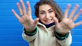 Красивая девушка при вьющиеся волосы играя с руками и усмехаясь около голубой стены сток-видео