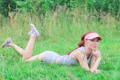 Красивая девушка при худенькая диаграмма лежа outdoors на Стоковые Изображения