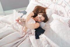 Красивая девушка просыпаясь самостоятельно в кровати, открытом космосе стоковые изображения