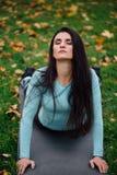Красивая девушка протягивая на траве Sporty молодая спортсменка брюнет на циновке йоги - верхней собаке облицовки Стоковое Фото
