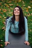 Красивая девушка протягивая на траве Sporty молодая спортсменка брюнет на циновке йоги Стоковые Фотографии RF