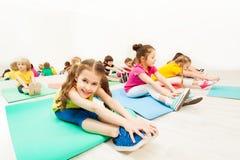 Красивая девушка протягивая ноги с друзьями в спортзале Стоковая Фотография RF