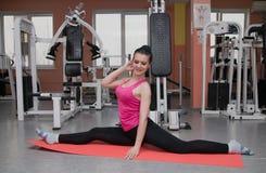 Красивая девушка работает в фитнес-клубе на половике Протягивать стоковая фотография rf
