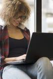 Красивая девушка работая на ее компьтер-книжке пока выпивающ кофе Стоковое фото RF