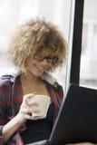 Красивая девушка работая на ее компьтер-книжке пока выпивающ кофе Стоковое Изображение