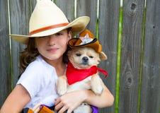 Красивая девушка ребенк ковбоя держа чихуахуа с шляпой шерифа Стоковое Изображение RF