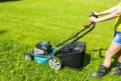 Красивая девушка режет лужайку, кося лужайки, травокосилку на зеленой траве, оборудовании травы косилки, кося инструмент работы з Стоковое Изображение RF
