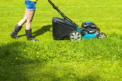 Красивая девушка режет лужайку, кося лужайки, травокосилку на зеленой траве, оборудовании травы косилки, кося инструменте работы  Стоковые Изображения RF