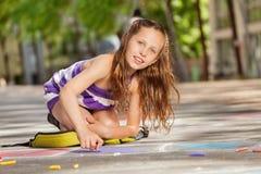 Красивая девушка рисует с мелом на асфальте Стоковое Изображение RF