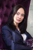 Красивая девушка сидит в кресле Стоковые Изображения