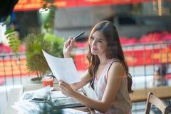 Красивая девушка сидит на балконе читая документ Стоковое фото RF
