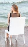 Красивая девушка сидит на белом стуле и смотрит море Очаровательная маленькая девочка сидит на предпосылке моря Стоковые Изображения RF