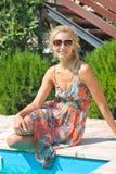 Красивая девушка сидит на крае бассейна стоковое изображение rf