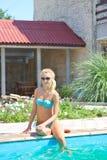 Красивая девушка сидит на крае бассейна стоковая фотография rf