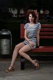 Красивая девушка сидит на скамейке в парке на предпосылке g стоковое фото