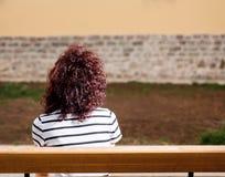 Красивая девушка сидит на скамейке в парке на предпосылке g стоковые изображения
