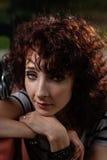 Красивая девушка сидит на скамейке в парке на предпосылке g стоковые фотографии rf
