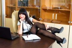 Красивая девушка сидя в офисе на столе Стоковая Фотография RF