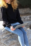 Красивая девушка сидя в парке с компьтер-книжкой и говоря на интернете Стоковое Изображение RF