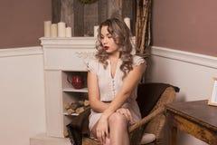 Красивая девушка сидя в стуле Стоковое Фото