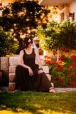 Красивая девушка сидя на лестницах в парке стоковое изображение