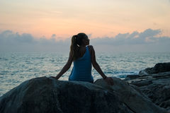 Красивая девушка сидя на камнях и смотря, что в расстоянии, девушке на заходе солнца размышлять в безмолвии, красивом теле Концеп Стоковые Фотографии RF