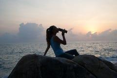 Красивая девушка сидя на камнях и смотря, что в расстоянии, девушке на заходе солнца размышлять в безмолвии, красивом теле Концеп Стоковое фото RF