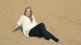 Красивая девушка сидя на пляже и смотря акции видеоматериалы