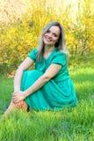 Красивая девушка сидя на лужайке стоковая фотография rf