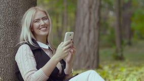 Красивая девушка сидя под деревом в парке осени усмехаясь и читая сообщения с сотовым телефоном в ее руках сток-видео